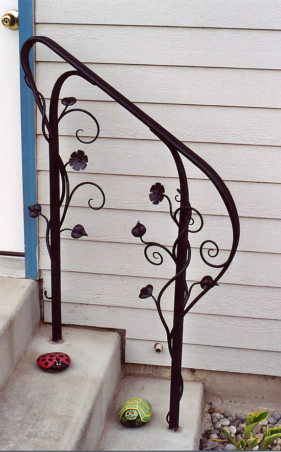 Exterior Handrail On Back Steps With Forged Flower Decorations.